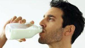 άντρας πίνει γάλα από γυάλινο μπουκάλι