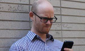 άντρας κοιτάει κινητό απορημένος