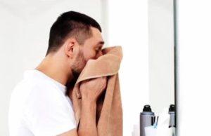 άντρας σκουπίζει το πρόσωπο του μετά από καθαρισμό προσώπου