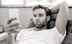 άντρας στέλνει μήνυμα στο κινητό