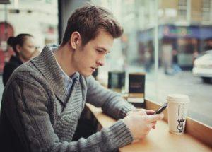 άντρας κοιτάει το κινητό του και στέλνει μήνυμα
