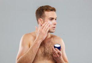 άντρας βάζει αντρική ενυδατική κρέμα
