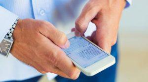 άντρας στέλνει μήνυμα με το κινητό του