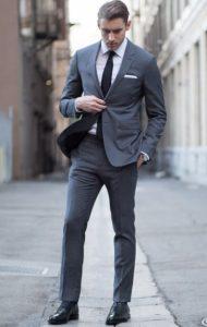 άντρας γκρι κοστούμι με λευκό πουκάμισο μαύρη γραβάτα
