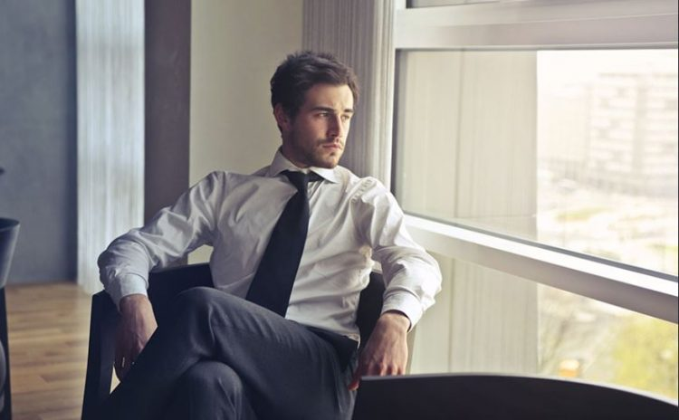 άντρας με κοστούμι σε καρέκλα κοιτάζει έξω από παράθυρο