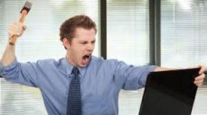 άντρας με σφυρί σπάει οθόνη υπολογιστή σε γραφείο