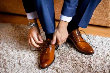 άντρας δένει καφέ παπούτσι
