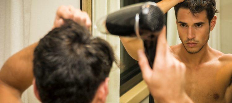 άντρας στεγνώνει μαλλιά με πιστολάκι πυκνά μαλλιά