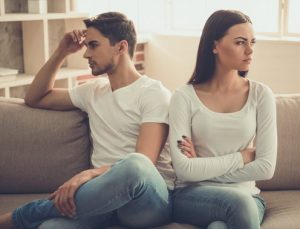 άντρας γυναίκα κοιτάνε αλλού κάθονται καναπέ