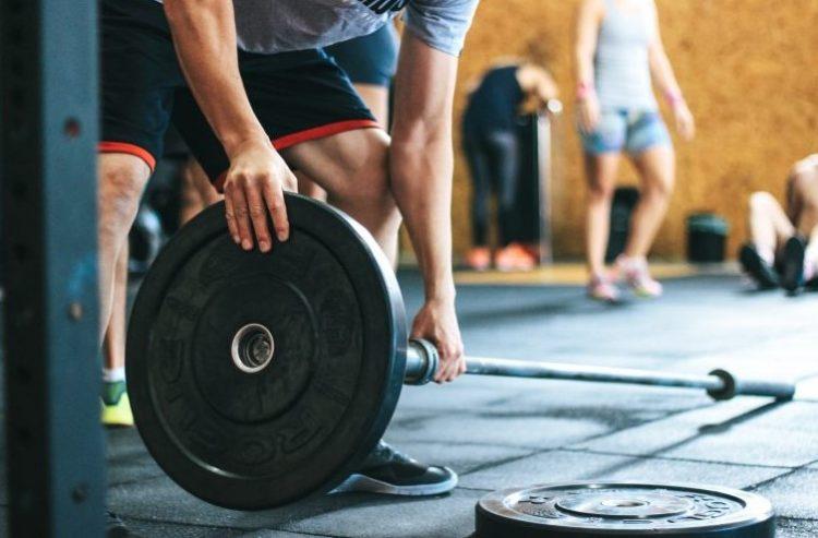 άντρας βάζει βάρη στη μπάρα τάσεις fitness