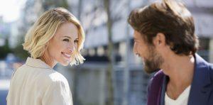γυναίκα χαμογελάει σε άντρα στο δρόμο
