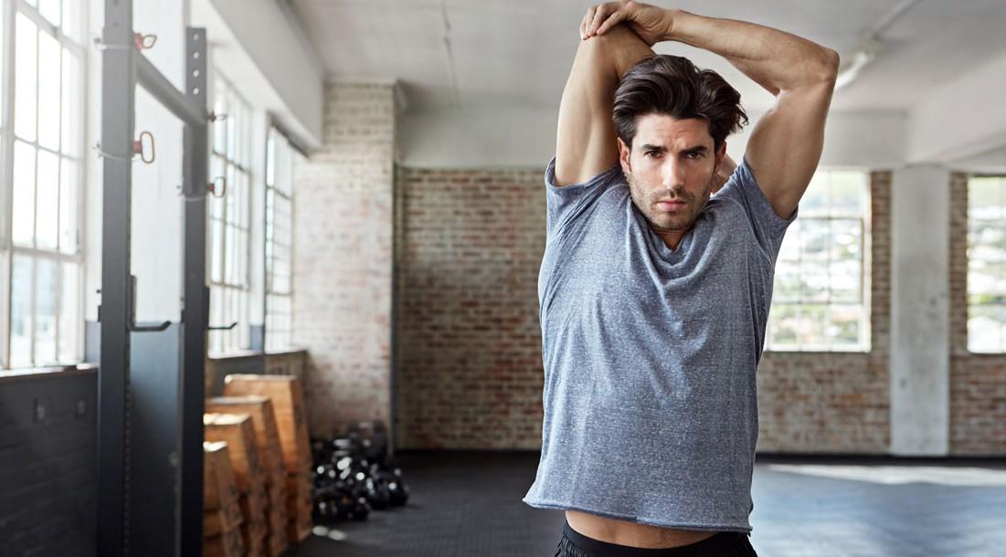 άντρας κάνει διατάσεις χέρια βελτιώσεις απόδοση γυμναστική