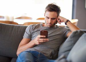 άντρας με το κινητό στον καναπέ