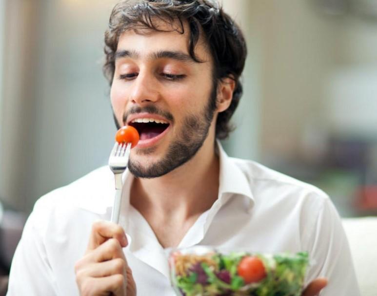 νέος άντρας πιρούνι ντομάτα