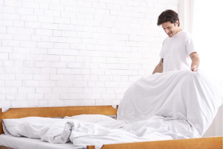 άντρας στρώνει το κρεβάτι του