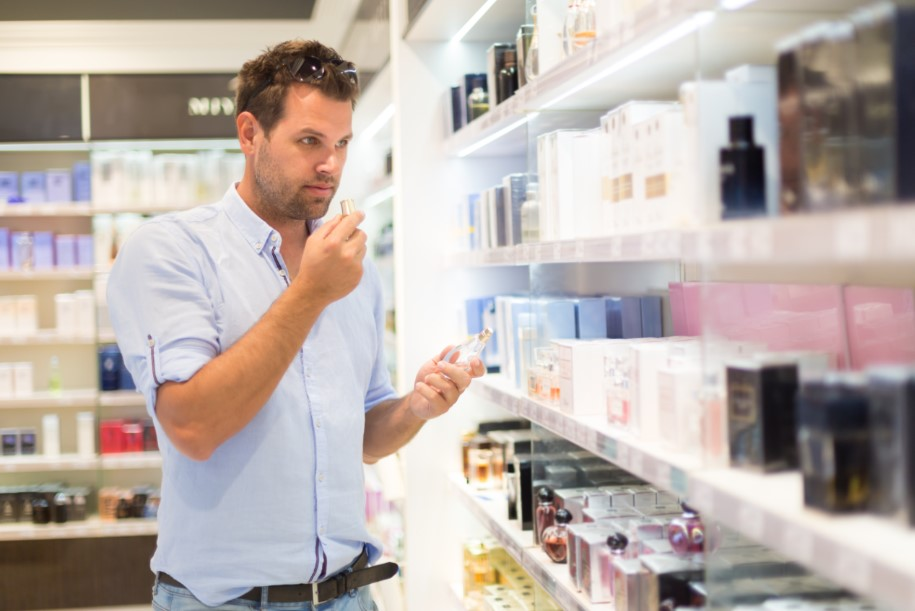 άντρας δοκιμάζει κολόνιες σε μαγαζί