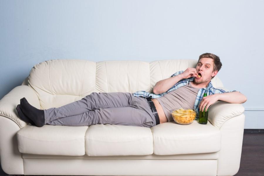 άντρας τρώει στον καναπέ