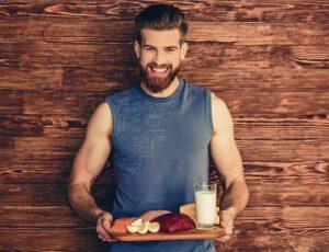 άντρας κρατάει δίσκο πρωτεϊνούχα τρόφιμα