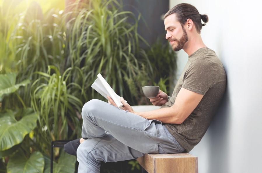 άντρας πίνει καφέ διαβάζοντας