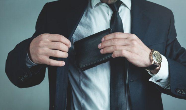 άντρας βάζει το πορτοφόλι του στη τσέπη