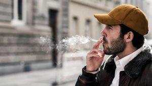 άντρας καπνίζει πορτοκαλί καπέλο