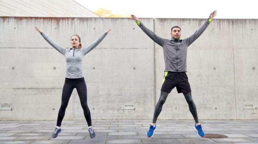 Δύο άτομα που κάνουν την αερόβια άσκηση, jumping jacks, σε ανοιχτό χώρο