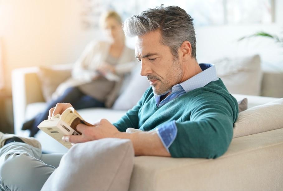 άντρας διαβάζει βιβλίο στον καναπέ
