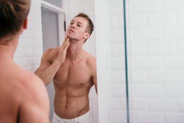 γυμνασμένος άντρας μπροστά από καθρέφτη