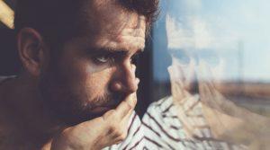 μελαγχολικός άντρας κοιτάει τζάμι