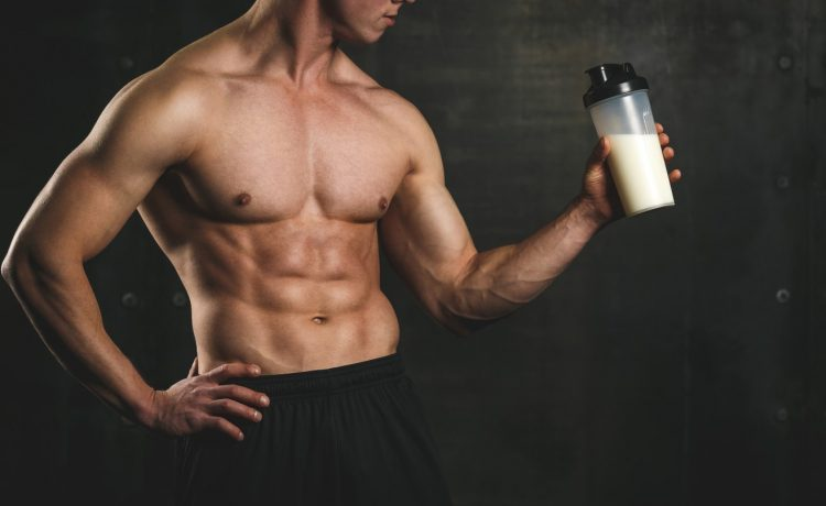 Άνδρας πίνει shaker για να πάρει τους υδατάνθρακες και τις απαραίτητες πρωτείνες
