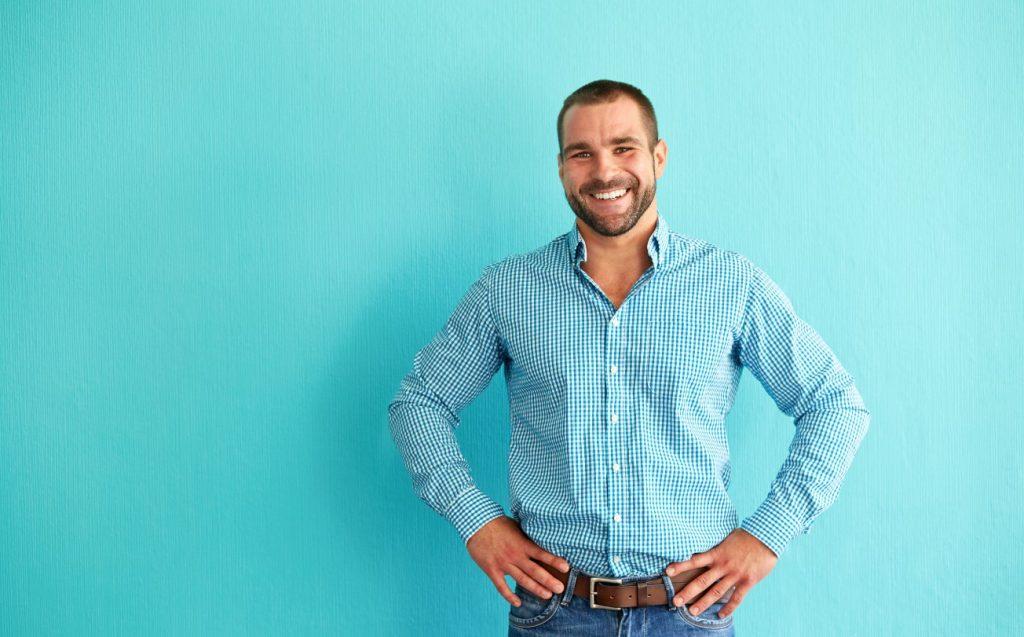 Χαρούμενος άνδρας που φοράει μπλε πουκάμισο και τζιν