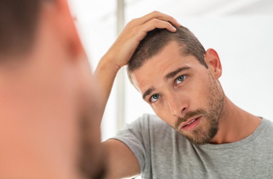 ανδρας κοιταζει τα μαλλια του
