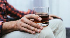 άντρας κρατάει ποτήρι αλκοόλ