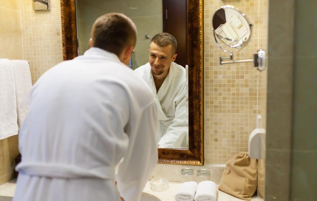 Άνδρας κοιτιέται στον καθρέφτη