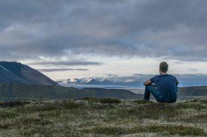 άντρας κάθεται μόνος του βουνό