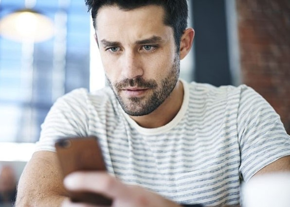 άντρας κρατάει κινητό