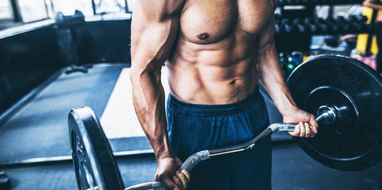 γυμνασμένος άντρας σηκώνει βάρη χτίσεις μύες