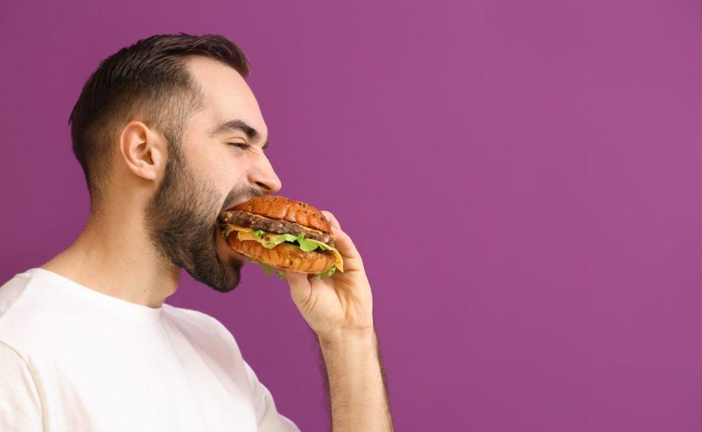 άνδρας τρώει burger: τι να αποφύγεις για να χάσεις βάρος
