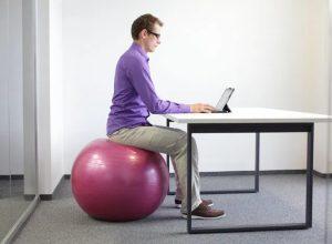 άντρας κάθεται σε μπάλα δουλεύει