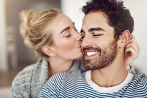 γυναίκα φιλάει άντρα μάγουλο σε βλέπει σοβαρά