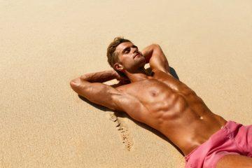 άνδρας κάνει ηλιοθεραπεία στην παραλία