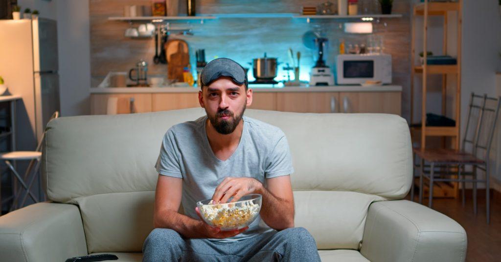 άνδρας τρώει αργά το βράδυ ποπ κορν
