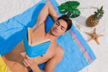 άντρας διαβάζει βιβλία παραλίας