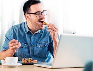 άντρας τρώει μπροστά στον υπολογιστή