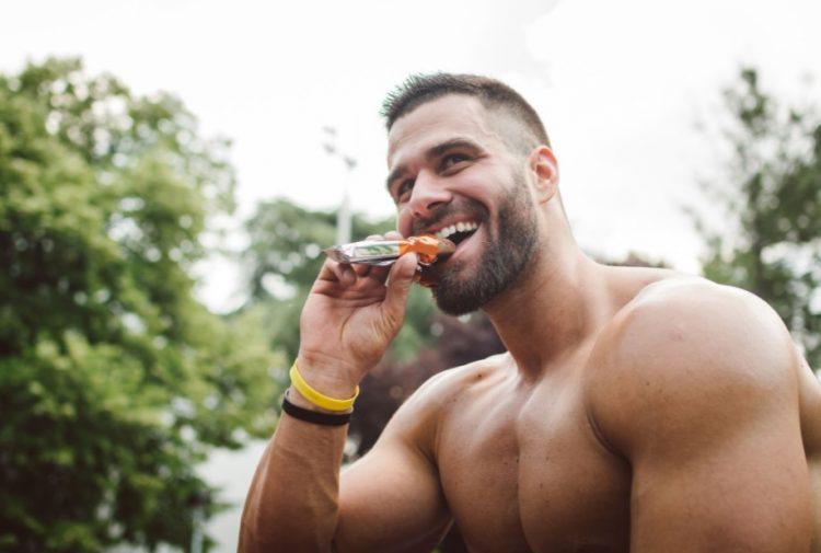 γυμνασμένος άντρας τρώει σνακ τροφές για περισσότερη ενέργεια
