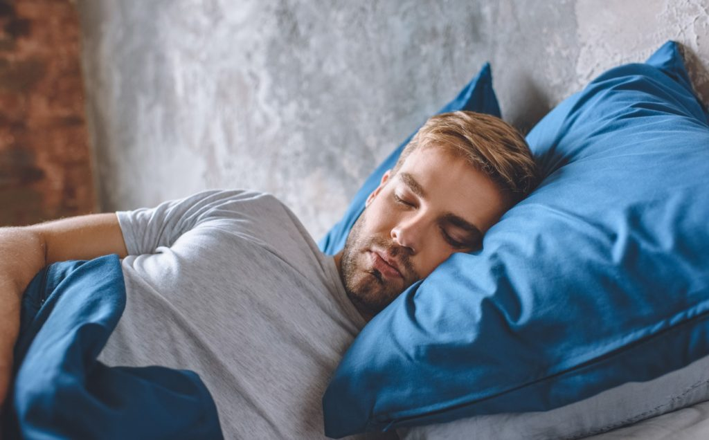 άνδρας κοιμάται στο κρεβάτι